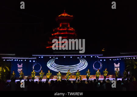 Dong people's dancing performance on stage, Drum Tower at back , Zhaoxing, Guizhou Province, China - Stock Photo
