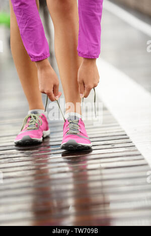 Running shoes. Barefoot running shoes closeup. Woman tying laces before jogging in minimalistic barefoot running shoes on Brooklyn Bridge, New York, USA. - Stock Photo