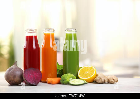Bottles with various fresh vegetable juices on table - Stock Photo