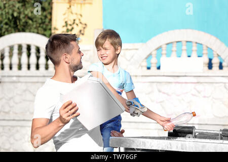 Man with son throwing garbage in metal container outdoors - Stock Photo