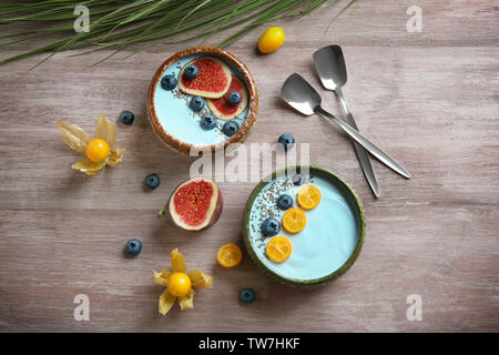 Bowls with yummy spirulina smoothie on wooden table. Healthy vegan food concept - Stock Photo