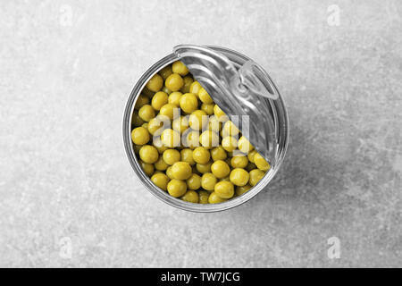 Open tin can with green peas on table - Stock Photo