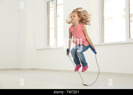 Cute girl skipping rope in light room - Stock Photo