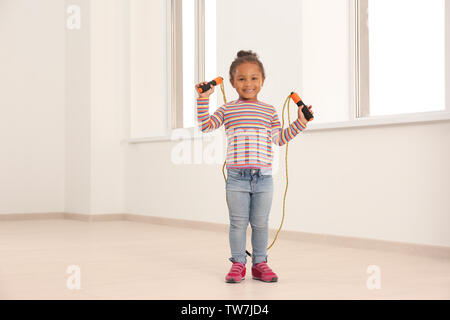 Cute African American girl skipping rope in light room - Stock Photo