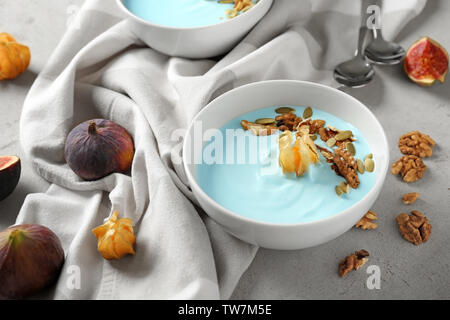 Bowl with blue spirulina smoothie on table. Healthy vegan food concept - Stock Photo