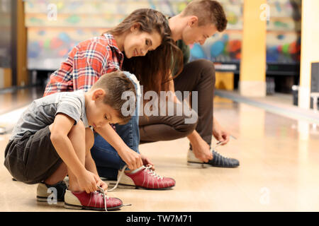 Family changing their shoes in bowling club - Stock Photo