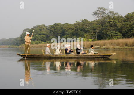 Tourists and their cameras enjoy a boat safari on the Rapti River in Chitwan National Park, Nepal - Stock Photo