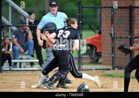 Runner being tagged out at the plate by the opposing catcher after the base runner was caught in a rundown between third and home. USA. - Stock Photo
