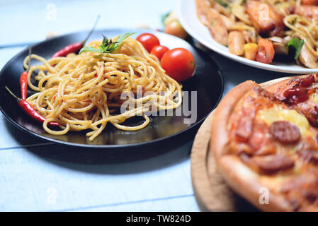 Spaghetti pasta and pizza on wooden tray / Traditional delicious Italian food spaghetti bolognese on plate on the dining table - Stock Photo