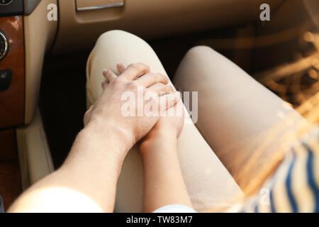 Young couple holding hands together in car - Stock Photo
