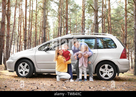 Young couple with their little children near car in pine forest - Stock Photo