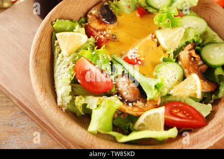 Delicious salad with honey mustard dressing in wooden bowl, closeup - Stock Photo