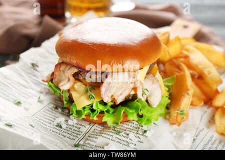 Tasty double burger on newspaper, closeup - Stock Photo