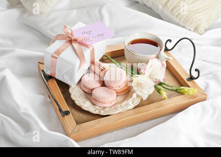 Wooden tray with breakfast and gift for Mother's day served in bed - Stock Photo