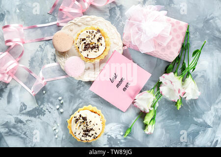 Composition with tasty desserts, gift box and greeting card for Mother's day on grey background - Stock Photo