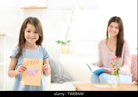 Little girl with gift for her mommy on Mother's Day indoors - Stock Photo