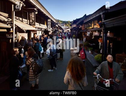 Kami-Sannomachi, old town market street of Takayama city busy with tourists. Kamisannomachi is a merchant town street lined with shops and restaurants - Stock Photo