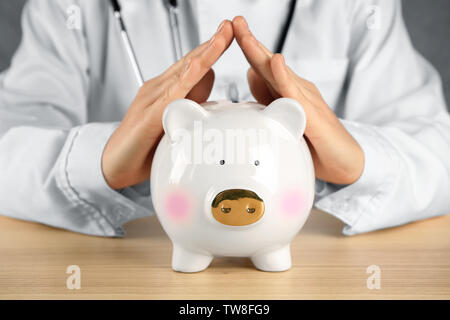 Doctor with piggy bank. Health insurance concept - Stock Photo