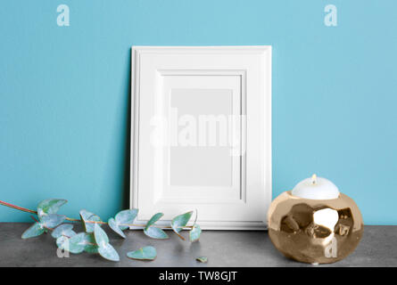 Empty white frame, candle and eucalyptus branch on table near color wall - Stock Photo