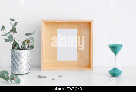 Empty wooden frame, hourglass and eucalyptus on table near white wall - Stock Photo