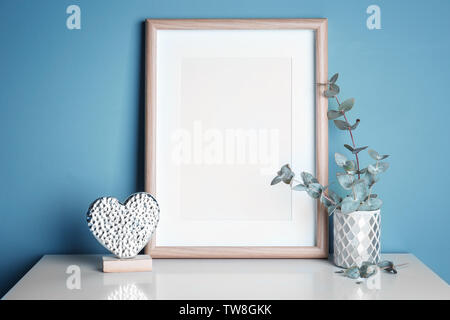 Empty wooden frame, decorative heart statuette and eucalyptus on table near color wall - Stock Photo