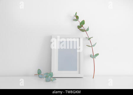 Empty frame and eucalyptus branch on table near white wall - Stock Photo