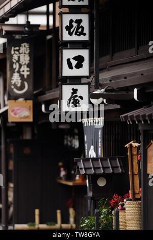 Shops and restaurants, closeup of signs at Kami-Sannomachi, old merchant town street in Takayama. Kamisannomachi historic town, Hida-Takayama, Japan - Stock Photo