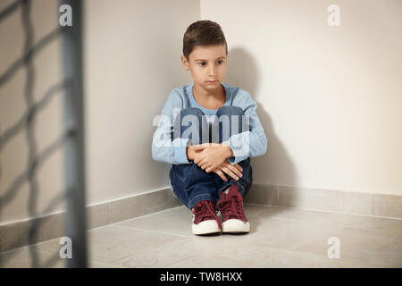 Upset little boy sitting on floor indoors - Stock Photo