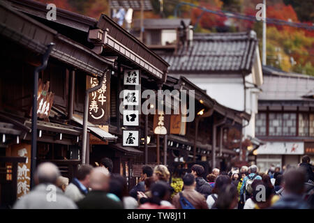 Signs of shops and restaurants at Kami-Sannomachi, old town market street of Takayama city busy with tourists and visitors in autumn. Kamisannomachi i - Stock Photo