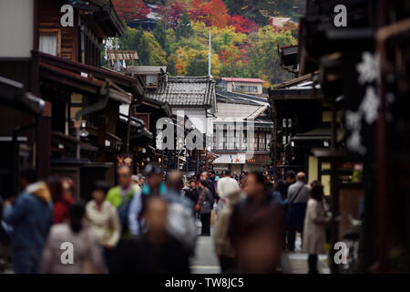 Shops and restaurants at Kami-Sannomachi, old town market street busy with tourists and visitors in autumn city scenery of Takayama, Gifu, Japan 2018. - Stock Photo