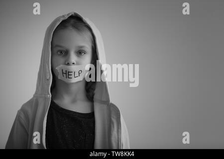 Sad little girl with taped mouth and word 'Help' on grey background, black and white effect - Stock Photo
