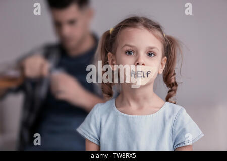 Sad little girl with taped mouth and her father drinking alcohol on background - Stock Photo