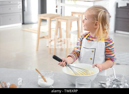 Cute little girl preparing dough indoors - Stock Photo