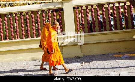 Phnom Penh, Cambodia - August 2016: Two monks in distinctive orange robe walking outside of Royal Palace. - Stock Photo