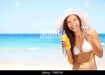 Sunscreen beach woman in bikini applying sun block solar cream for UV protection. Girl smiling to camera, wearing white sun hat, happy on vacation travel holiday. Hawaii, USA - Stock Photo