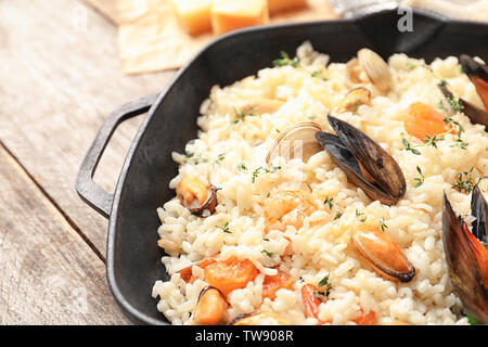Frying pan with delicious seafood risotto on wooden table - Stock Photo