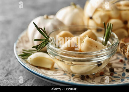 Preserved garlic in glass bowl on plate - Stock Photo