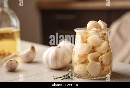 Preserved garlic in glass jar on table - Stock Photo