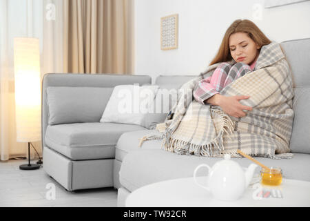 Sick woman wrapped in warm blanket at home. Honey and cup of tea on table near her - Stock Photo