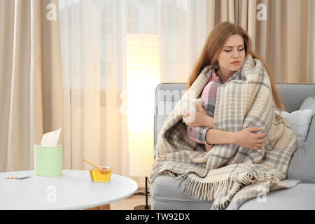 Sick woman wrapped in warm blanket at home. Bowl of honey on table near her - Stock Photo