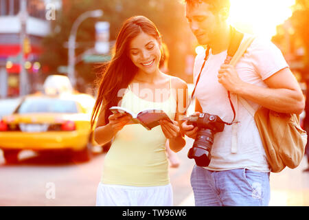 Travel tourist couple traveling in New York reading guide book standing with SLR camera at sunset on Manhattan with yellow taxi cab in the background. Happy young multiracial couple on summer holidays - Stock Photo