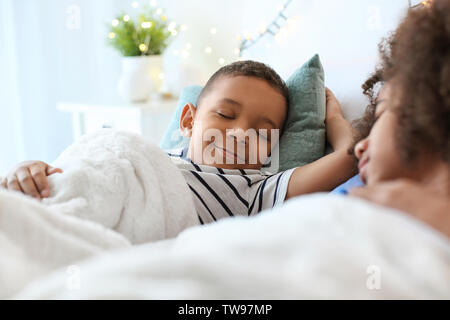 Cute African American children sleeping in bed. Family bedtime Stock Photo