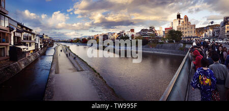Kyoto Shijo bridge full of people and a path along the banks of Kamo River, Kamo-gawa, in a beautiful panoramic autumn city scenery. Kyoto, Japan 2017 - Stock Photo