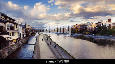 Walkway along the banks of Kamo-gawa, Kamo River in Kyoto in a panoramic sunset autumn city scenery. Kyoto, Japan 2017 - Stock Photo
