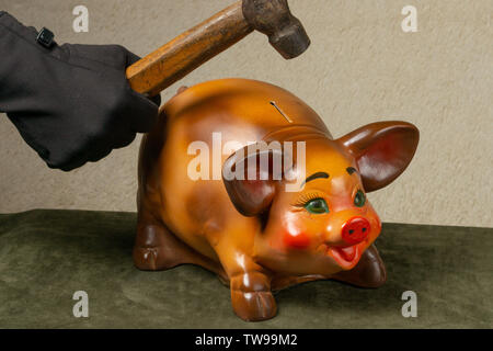 hand with a hammer breaks piggy bank - Stock Photo