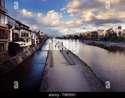Walkway along the banks of Kamo-gawa, Kamo River in Kyoto in a sunset autumn city scenery. Kyoto, Japan - Stock Photo