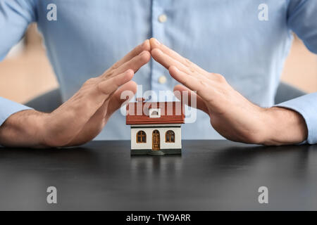 Insurance concept. Man with toy house on table - Stock Photo