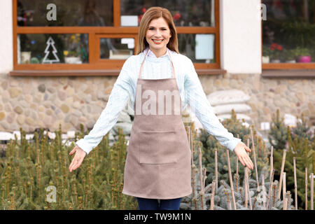 Business owner near plants in her store, outdoors - Stock Photo