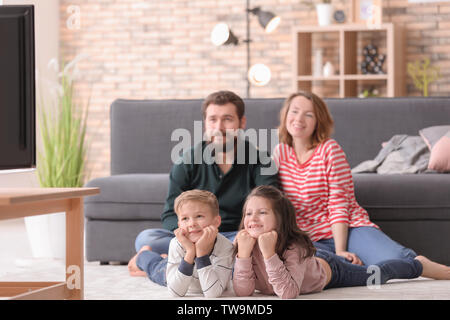 Happy family watching TV at home - Stock Photo