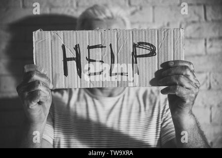 Poor man holding sign with word HELP on brick wall background. Black and white effect - Stock Photo